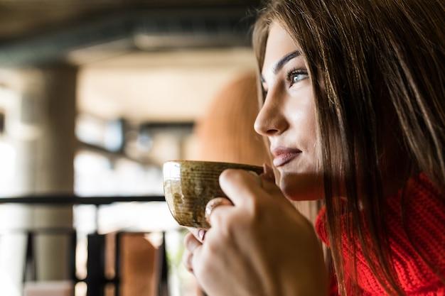 Молодая женщина пьет кофе утром в ресторане