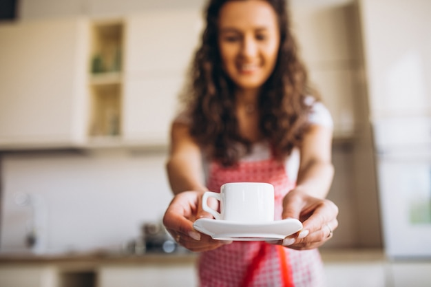 Young woman drinking coffee at the kitchen in the morning