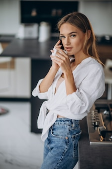 Young woman drinking coffee at the kitchen