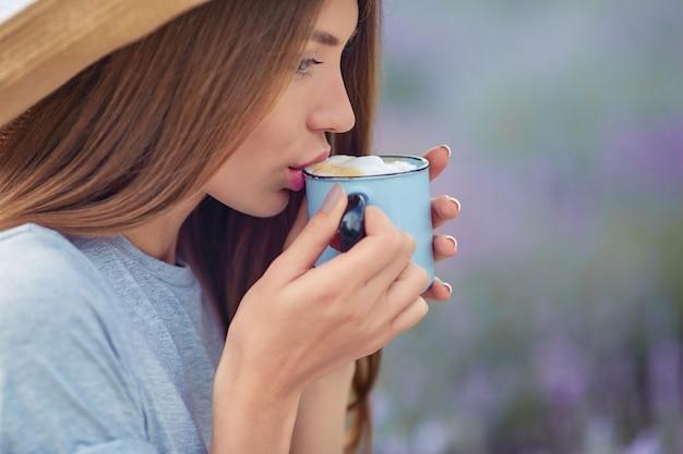 Giovane donna che beve caffè nel campo di lavanda