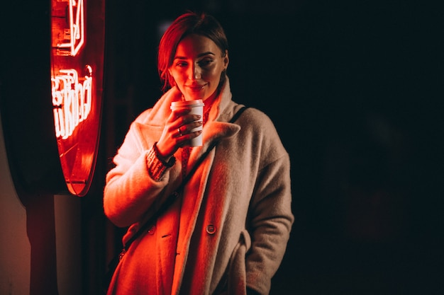 Young woman drinking coffee at night street