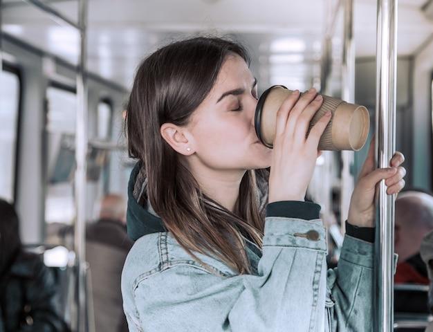 公共交通機関でコーヒーを飲む若い女性。