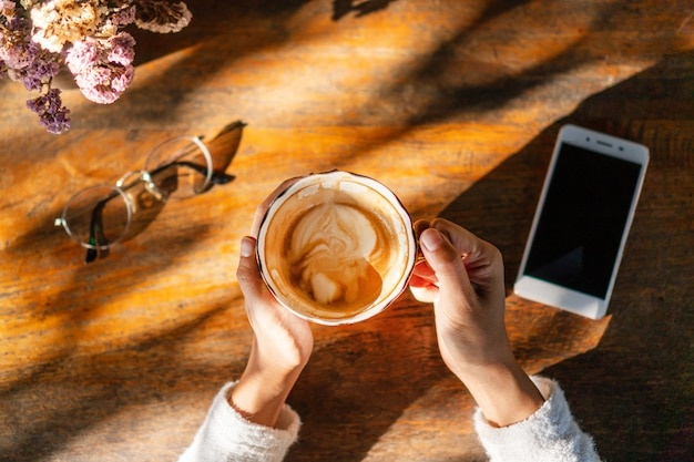 スマートフォンと自由時間中にカフェでメガネの木製テーブルでコーヒーを飲む若い女性。
