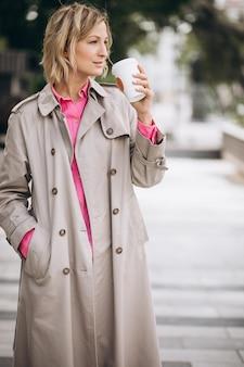市内でコーヒーを飲みながら若い女性