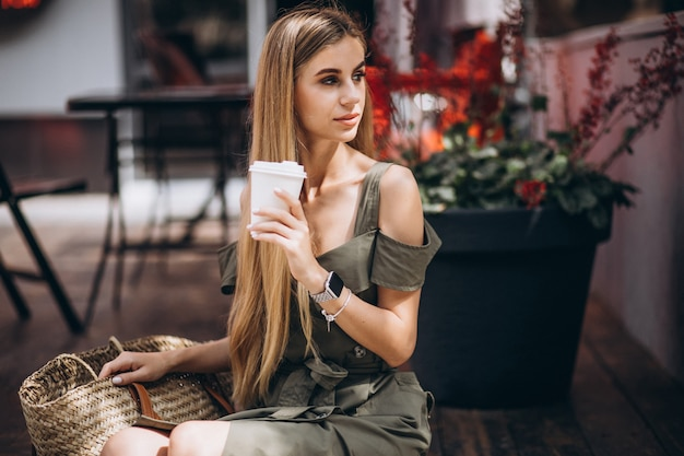 Young woman drinking coffee outside the cafe