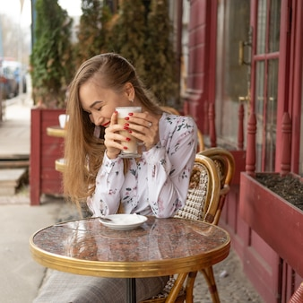 Young woman drinking coffee in a parisian street cafe