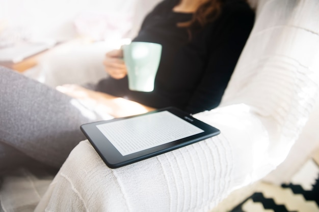 Young woman drinking coffee and using an ebook reader