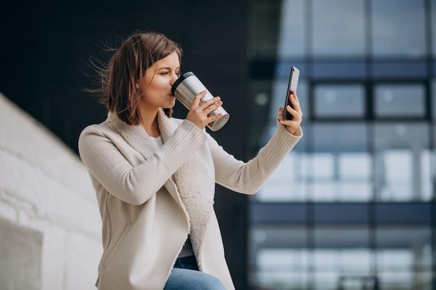 Caffè bevente della giovane donna e telefono usando usando fuori della via