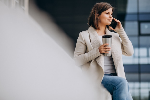 Young woman drinking coffee and using phone outside the street
