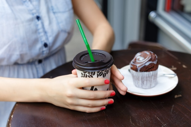 Young woman drinking coffee with muffin in outdoors cafe, close up