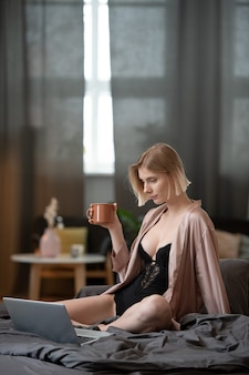 Young woman drinking coffee and working online on laptop while sitting on the bed in the bedroom