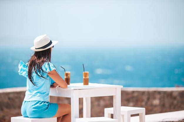 Молодая женщина пьет холодный кофе, наслаждаясь видом на море в летнем кафе