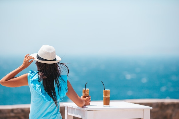 Young woman drinking cold coffee enjoying sea view in outdoor cafe
