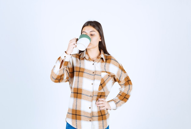 Young woman drinking cup of coffee on white wall.
