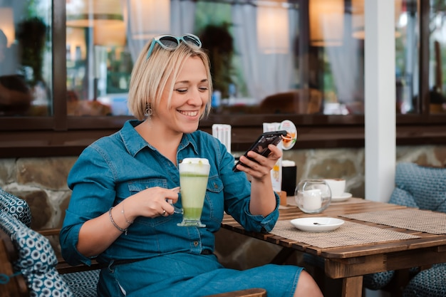 Young woman drinking enjoying matcha green tea latte in summer morning in cafe talks on a mobile phone smartphone