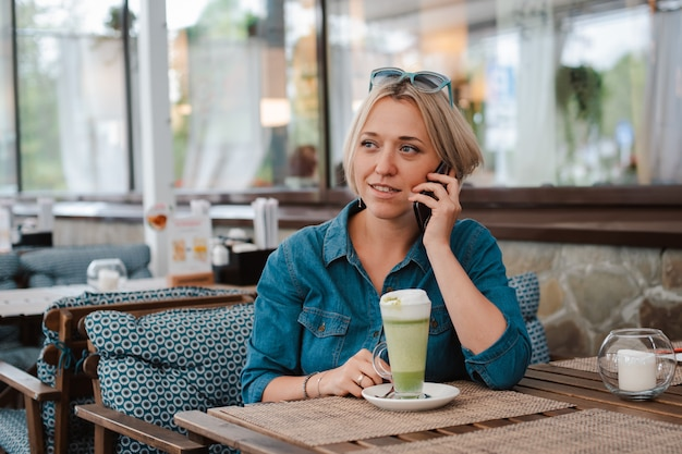 Young woman drinking enjoying matcha green tea latte in summer morning in cafe.