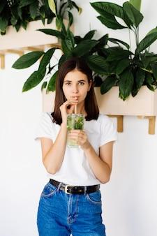 Giovane donna che beve bevanda fresca in caffè