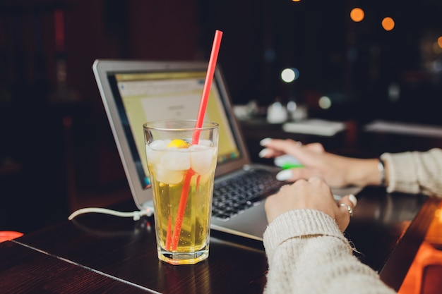 Young woman drinking fresh lemonade while working on laptop in cafe, closeup.