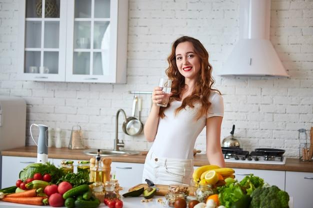 若い女性が台所でガラスから新鮮な水を飲みます。健康的なライフスタイルと食事。健康、美容、ダイエットのコンセプトです。