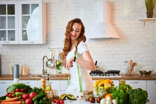 キッチンでガラスからキュウリ、レモン、ミントの葉で新鮮な水を飲む若い女性。健康的なライフスタイルと食事。健康、美容、ダイエットのコンセプトです。