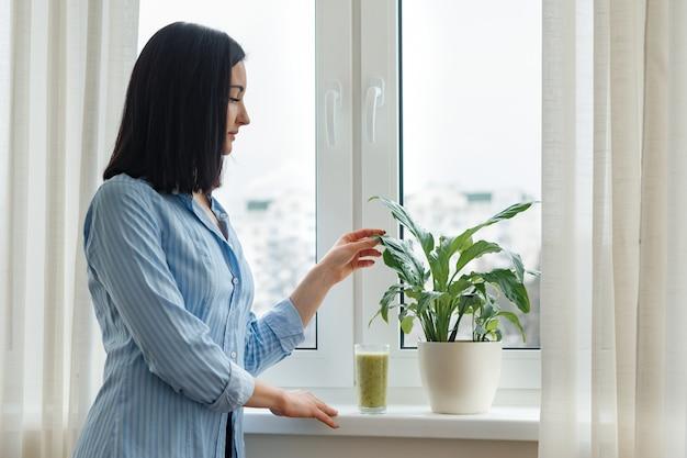 Молодая женщина пьет свежевыжатый зеленый киви смузи
