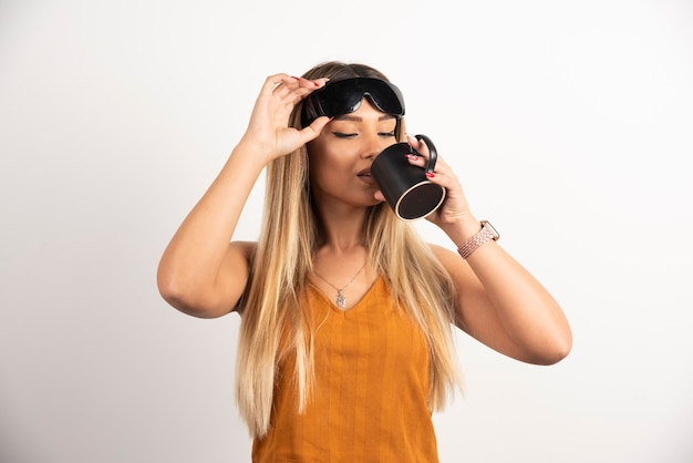 Young woman drinking from black cup and wearing goggles.