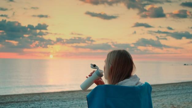 サーマルマグから飲んで、日の出の後ろの景色の前にビーチに座っている若い女性