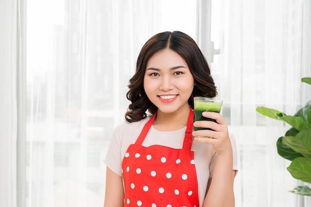 緑のカクテルを飲む若い女性
