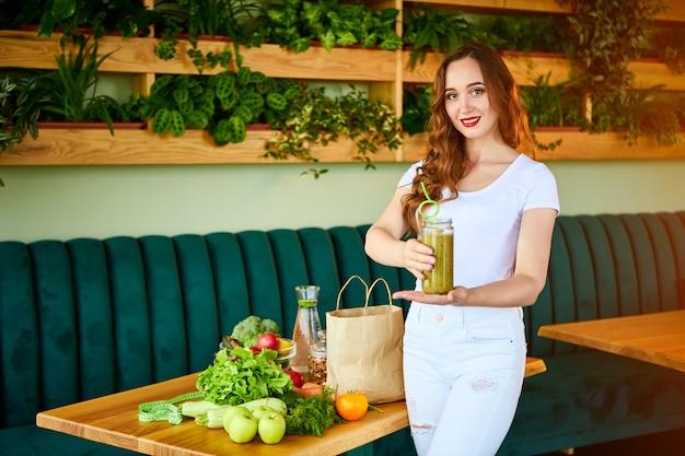 果物と野菜で台所のテーブルに緑のスムージーを飲む若い女性。健康的な食事のコンセプトです。ビーガンミールとデトックスメニュー