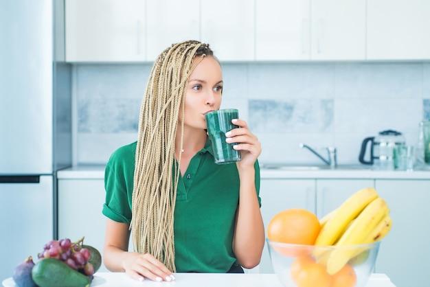 녹색 스무디를 마시는 젊은 여자