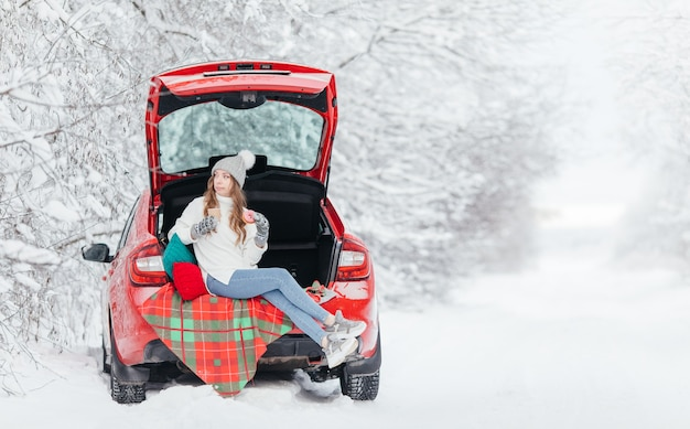 Young woman drinking hot drink, coffee, cocoa or tea from a paper cup and eating donat cake while sitting in the trunk of a red car on the background of a winter forest