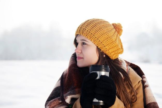 야외에서 뜨거운 음료를 마시는 젊은 여자