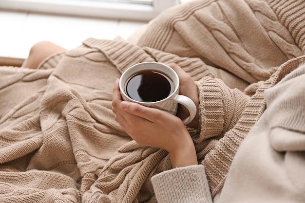 Молодая женщина пьет горячий чай дома