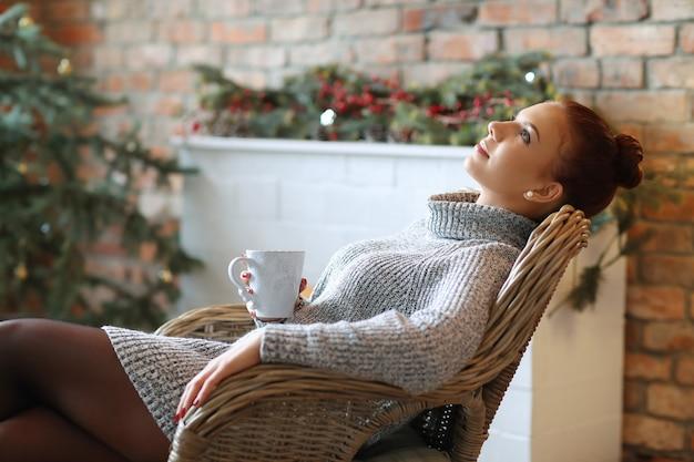 ソファーで熱いお茶を飲む若い女性