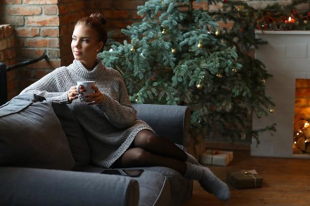 Молодая женщина пьет горячий чай на диване