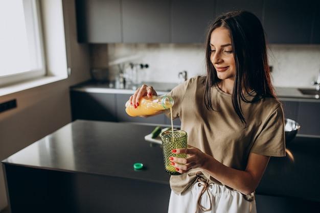 Giovane donna che beve succo di frutta a casa