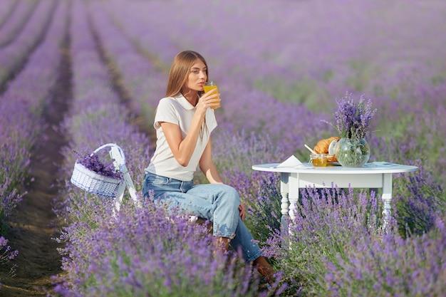 ラベンダー畑でジュースを飲む若い女性