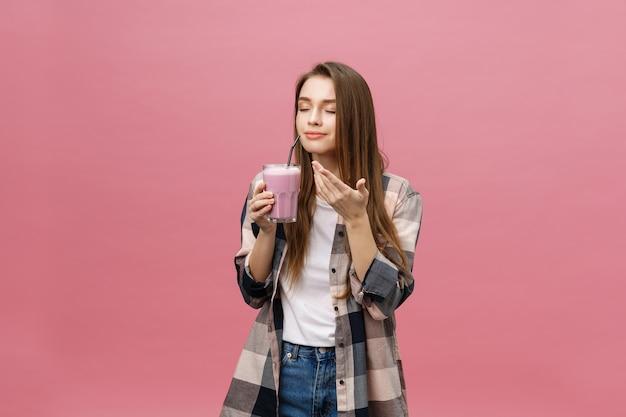 Молодая женщина пьет сок смузи с соломинкой