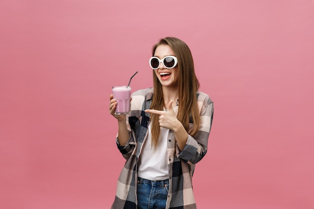 Молодая женщина пьет сок смузи с соломинкой Premium Фотографии