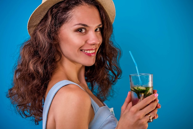 Young woman drinking lemonade on blue wall
