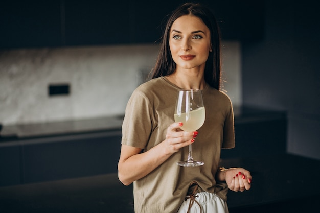台所でガラスからレモネードを飲む若い女性