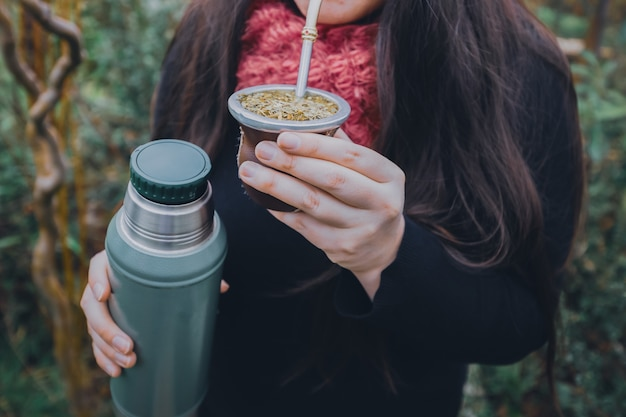 Young woman drinking mate in the park latin beverage ethnical concept high quality photo
