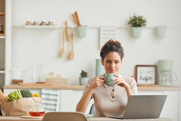Молодая женщина пьет утренний кофе и смотрит на монитор ноутбука, сидя на кухне дома