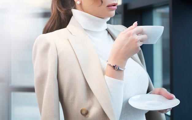 창문 가까이 모닝 커피를 마시는 젊은 여자