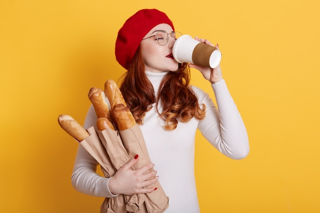 Young woman drinking take away coffee from disposable cup and holding paper bags with fresh baguettes on yellow
