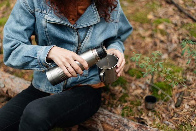 Young woman drinking tea in cup. woman pours a drink into a mug from a thermos. girl drinking tea while hike.traveler girl pouring tea from a thermos cup, outdoors.