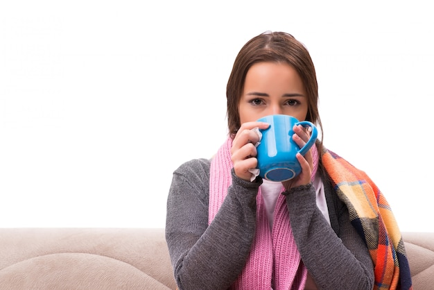 Young woman drinking tea during fever
