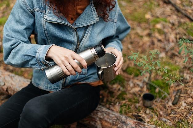 Молодая женщина пьет чай в чашке. женщина наливает напиток в кружку из термоса. девушка пьет чай во время похода. девушка-путешественница разливает чай из термоса, на открытом воздухе.