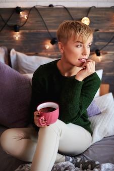 Giovane donna che beve il tè nella giornata invernale