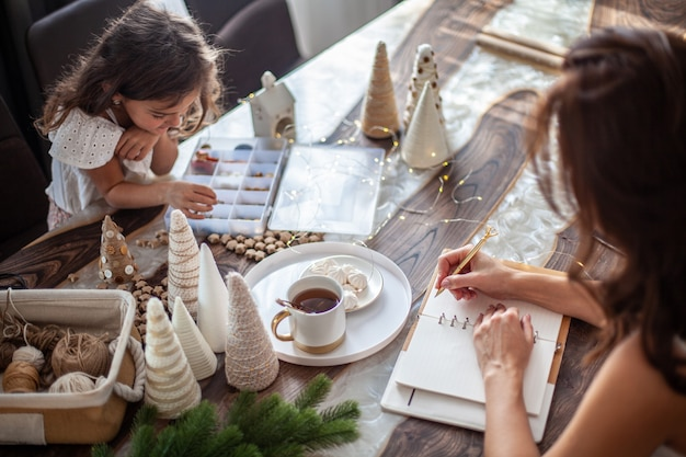 Young woman drinking tea and writing plans or goals for new year 2021 while her daughter crafting christmas trees from paper cone, yarns and buttons with placed stars and fairy lights on wooden table.